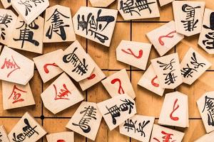 将棋盤の上に載った将棋駒の数々の画像