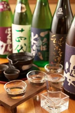 日本酒の一升瓶、ぐい飲みが並ぶ光景画像